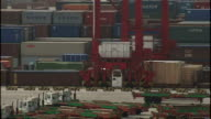 Exterior shots of shipping containers being moved around by truck and crane at Shanghai deep water port on October 21 2008 in Shanghai China