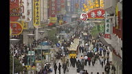Exterior shots of shoppers a businessman smoking a cigar people on mobile phones on April 18 2000 in Shanghai China