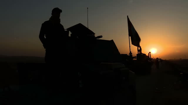 Exterior shots of silhouettes against a sunset background of the Iraqi army Golden division in armoured vehicles clearing and patrolling the area...