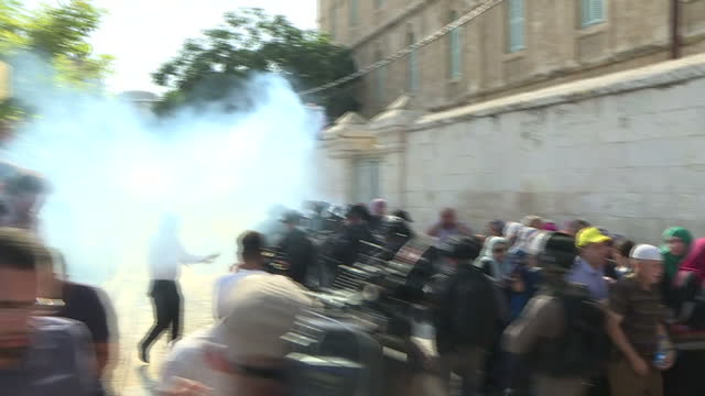 Exterior shots of smoke grenades exploding and riot police charging towards protesters as tensions flare near Temple Mount on 27 July 2017 in...