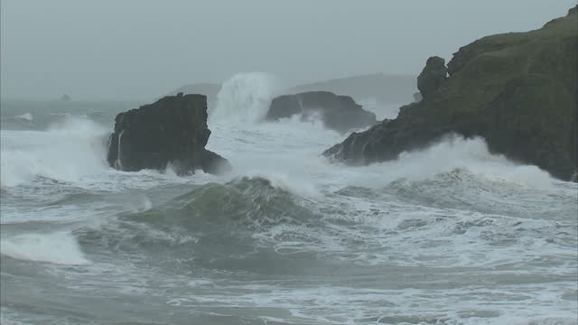 Exterior shots of stormy waves crashing on Porthcothan rocks remains of natural stone archway brought down by storm waves waves crashing on a beach...