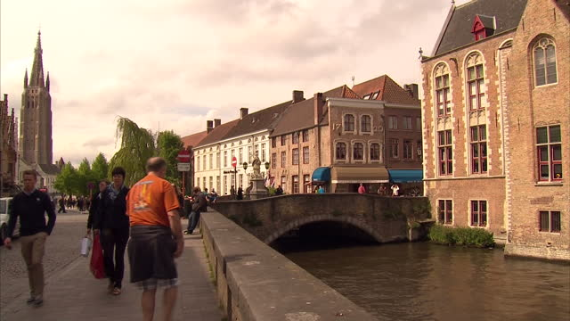Exterior shots of streetscenes in the city of Brugge including tourists on a river cruise iconic landmarks Basilica of the Holy Blood the Church of...