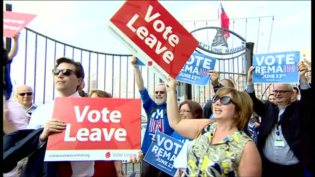 Exterior shots of 'Stronger IN' campaigners holding up placards for vote remain shots of 'Vote Leave' campaigners holding up placards next to 'Vote...