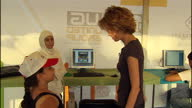 Exterior shots of Syrian First Lady Asma Al Assad speaking to young people working on computer technology programs and greeting young children on...