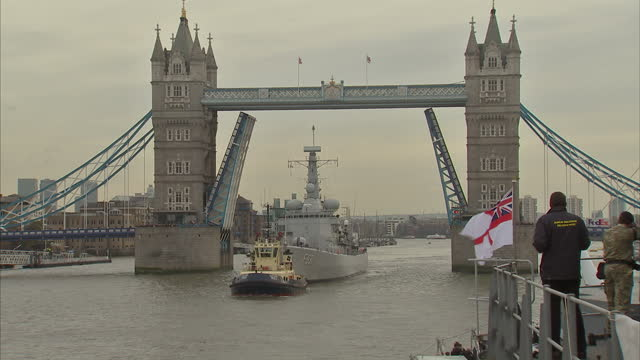 Exterior shots of the Belgian frigate LouiseMarie passing under Tower Bridge and mooring alongside the HMS Belfast and officers carrying sandbags...