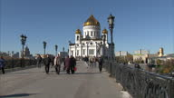 Exterior shots of the Cathedral of Christ the Saviour with pedestrians walking across the footbridge in the foreground and showing its gilded domes...