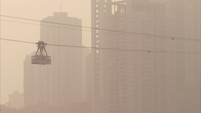 Exterior shots of the Chongqing city skyline shrouded in smog and cable cars crossing the river Wide shots of Chongqing city skyline on October 17...
