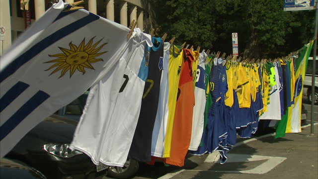Exterior shots of the Estadio do Pacaembu stadium as a football fan hangs out the shirts of various national teams on a washing line in front of it...