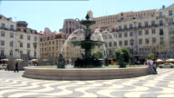 Exterior shots of the fountain in Rossio Square with pigeons sitting on its edge on May 11 2007 in Lisbon Portugal