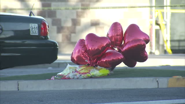Exterior shots of the police cordon near the scene of the mass shooting attack on a country music concert including shots of heart shaped balloons...