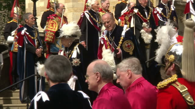 Exterior shots of the Queen and Prince Philip walking down the steps of St George's Chapel after attending the annual service for the Order of the...