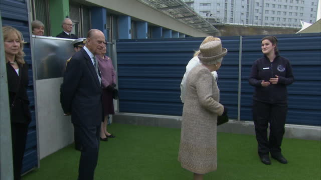 Exterior shots of the Queen and Prince Philip watching a member of staff demonstrating dog obedience training during a visit to Battersea Dogshome>>...