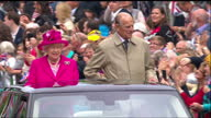 Exterior shots of the Queen and Prince Philip waving from the back of an opentop Range Rover to cheering crowds on The Mall followed by Prince...