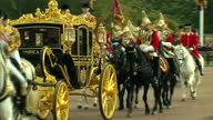 Exterior shots of The Queen in back of carriage in procession with Royal Guards on horseback arriving at Buckingham Palace on October 21 2014 in...