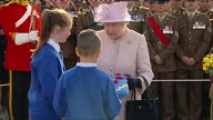 Exterior shots of the Queen receiving a posy of flowers and a cushion featuring a poppy pattern from local children during a visit to the new...