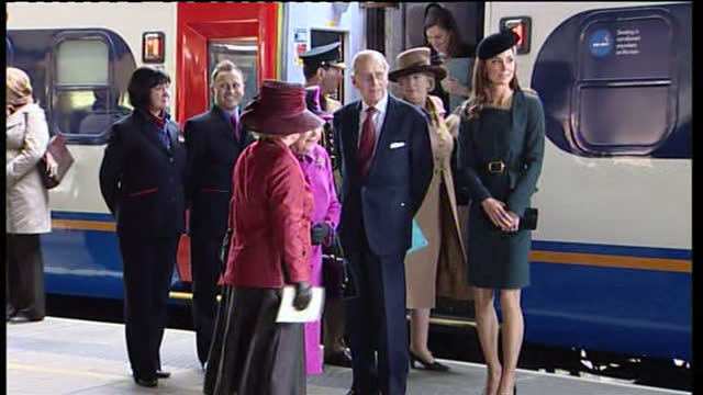 Exterior shots of The Queen wearing purple outfit stepping off train with Catherine Middleton and Prince Philip and greeting officials on platform...