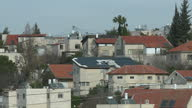Exterior shots of the rooftops of residential buildings on the outskirts of Ramallah with a Palestinian flag flying from a building and Palestinian...
