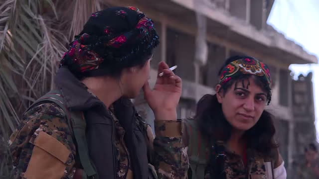 Exterior shots of the rubble of central Raqqa with various devastated buildings and a group of YPG women fighters dancing to music after the city's...