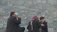 Exterior shots of the Sanlirfa or Urfa skyline with local men and youths speaking together smoking and eating snacks>> on March 10 2015 in Sanliurfa...