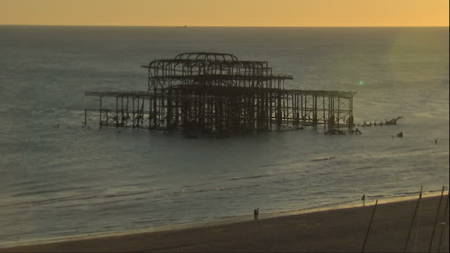 Exterior shots of the setting sun shining on the sea at Brighton beach near the skeletal remains of the West Pier which was destoyed by fire in...