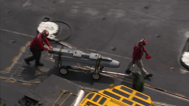 Exterior shots of the USS Carl Vinsons Ordnancemen moving a Walleye laser guided bomb smart bomb precision guided munition across flight deck on...
