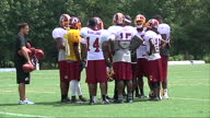 Exterior shots of the Washington Redskins American football team warming up and training on pitch watched by onlookers stretching and passing balls...