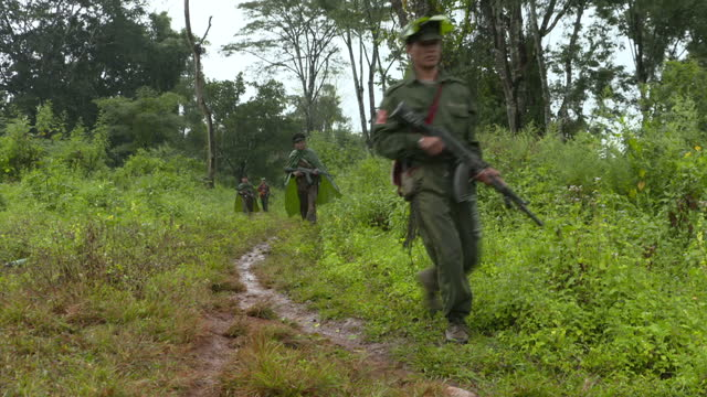 Exterior shots of TNLA rebel soldiers walking through a Myanmar jungle holding automatic rifles on November 05 2015 in Yangon Burma