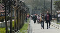 Exterior shots of tourists and families walking through a park near the Sultan Ahmet Mosque known as the Blue Mosque on April 15 2017 in Istanbul...