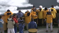 Exterior shots of tourists on an expedition through the North West passage looking out at Ice Floes taking pictures on the bow of an Icebreaker on...