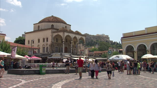 Exterior shots of tourists walking around near market stalls selling hats on July 10 2015 in Athens Greece