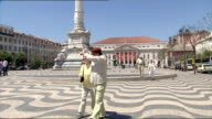 Exterior shots of tourists walking around Rossio Square and taking photos of the Gil Vicente monument on a sunny day on May 11 2007 in Lisbon Portugal