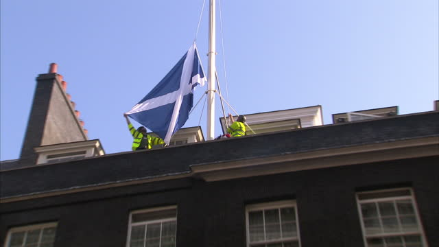 Exterior shots of two men attaching the Scottish blue and white flag to the pole on top of 10 Downing Street raising it to the top Larry the cat...