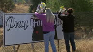 Exterior shots of two women leaving floral tributes at a sign with the slogan 'Pray For Roseburg' near Umpqua Community College where nine people...