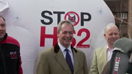 Exterior shots of UKIP Leader Nigel Farage campaigning in Wendover posing with a billboard pledging that 'UKIP will stop HS2 before it runs out of...
