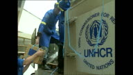 Exterior shots of UNHCR convoy delivering aid and people unloading boxes from UNHCR trucks in June 1992 in Sarajevo Bosnia and Herzegovina