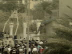 Exterior shots of US army and Iraqi locals pulling down statue of Saddam Hussein with rope around neck and then jump on statue celebrating the fall...