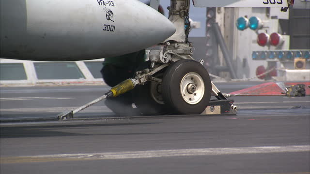 Exterior shots of USS Carl Vinson Aircraft carrier flight deck crew attaching a US Fighter Jet nose gear to the aircraft catapult and taking off on...