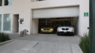 Exterior shots of various BMW automobiles pulling out of a BMW Dealership in Mexico City Mexico
