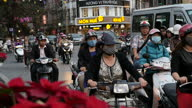 Exterior shots of very busy rush hour Hanoi traffic with lots of commuters on scooters and in cars passing through a packed intersection various...