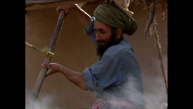 Exterior shots of village life in Afghanistan with maize being washed and bread being baked in a traditional clay oven on October 29 2001 in Kabul...