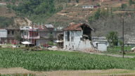 Exterior shots of villagers picking up building rubble with their hands and buildings completely destroyed by a major earthquake that hit the area...