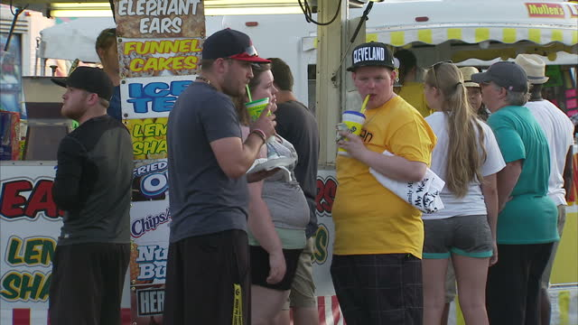 Exterior shots of visitors the hte Trumbull County Summer Fair buying various fast food snacks and drinks on the eve of the Republican Convention on...