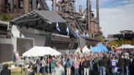 Exterior shots of visitors to an Oktoberfest beer festival event drinking beer and socialising in front of the derelict buildings and pipework of the...