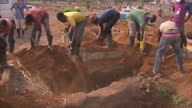 Exterior shots of volunteers burying the body of an Ebola victim in a rural part of Sierra Leone on January 12 2015 in Freetown Sierra Leone