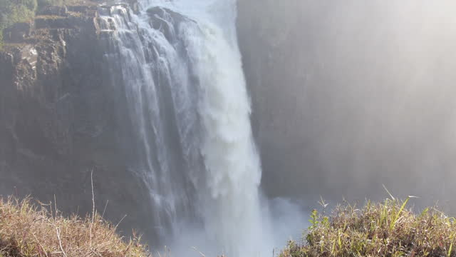 Exterior shots of water tumbling over Victoria Falls on the Zambezi River with clouds of spume or spray in the air and a rainbow visible on August 07...
