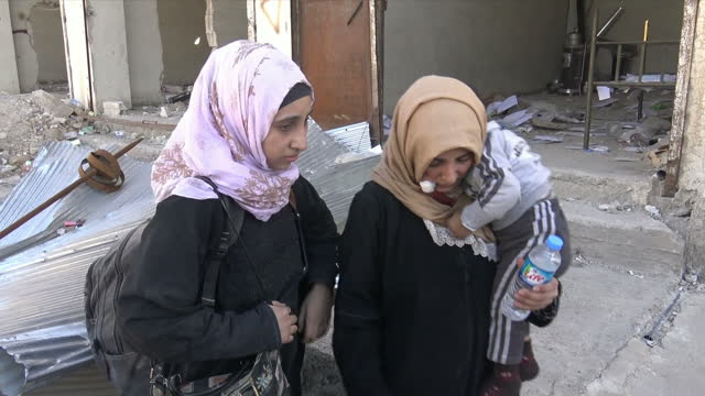 Exterior shots of women and children sat on the ground amidst rubble as YPG soldiers assist them on 17 October 2017 in Raqqa Syria