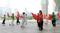 Exterior shots of women outside a large building doing morning exercises Tai Chi on September 20 2015 in Shenzhen China