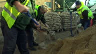 Exterior shots of workers filling sandbags at a depot near Shepperton and a 4x4 vehicle driving along a flooded road Flood levels continue to rise...