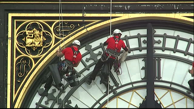 Exterior shots of workmen in climbing harnesses hanging from the Elizabeth Tower of the Houses of Parliament to carry out cleaning work on the face...