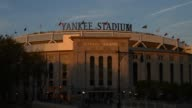 Exterior shots of Yankee Stadium during the day in Bronx New York Shots pan across the façade of Yankee Stadium as vehicle traffic passes over the...